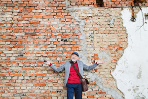 Handsome senior man in gray jacket holding smart phone. Orange brick wall background.