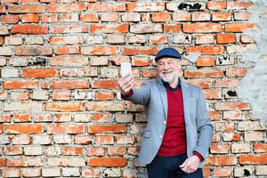 Handsome senior man in gray jacket holding smart phone, taking selfie. Orange brick wall background.