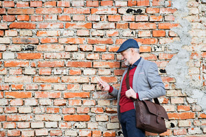 Handsome senior man in gray jacket holding smart phone, texting. Orange brick wall background.