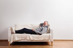 Handsome senior man in gray sweater smiling, lying on sofa, legs crossed. Studio shot against white wall.