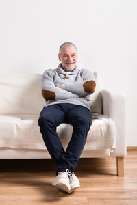 Handsome senior man in gray sweater smiling, sitting on sofa, resting, arms and legs crossed. Studio shot against white wall.