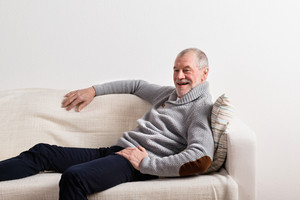 Handsome senior man in gray sweater smiling, sitting on sofa, resting. Studio shot against white wall.