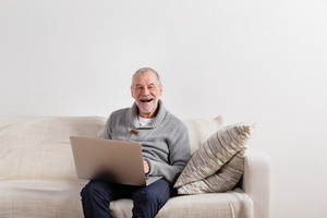 Handsome senior man in gray sweater smiling, sitting on sofa, working on laptop. Studio shot against white wall.