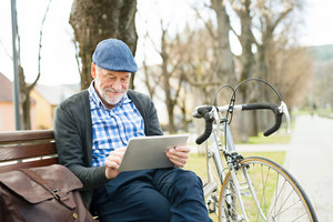Handsome senior man with bicycle in town park sitting on bench, working on tablet. Sunny spring day.