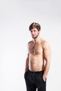 Handsome shirtless fitness man, hands in pockets. Studio shot on gray background.