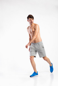 Handsome shirtless fitness man wearing gray shorts. Studio shot on gray background.