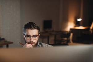 Handsome young bearded web designer dressed in shirt working late at night and looking at computer.