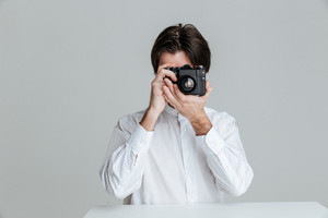 Handsome young brunette man sitting at the table and making photo with camera isolated on the gray background