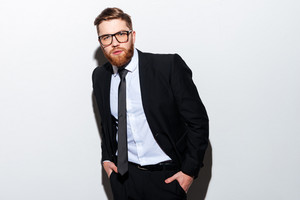 Handsome young business man in glasses and black suit posing with arms in pockets and looking at camera. Isolated gray background