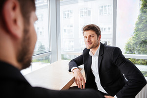 Handsome young businessman sitting and talking with his colleague in office
