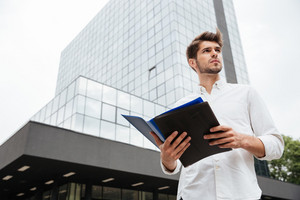 Handsome young businessman standing and holding documents in folder outdoors