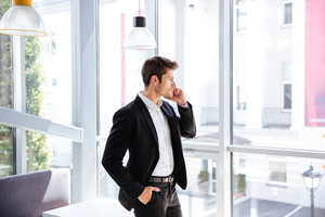 Handsome young businessman standing near the window and talking on cell phone