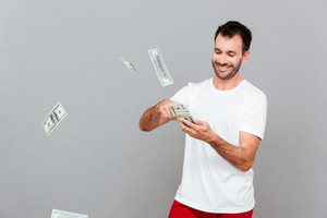 Handsome young casual man counting money over gray background