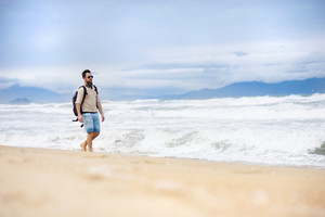 Handsome young Caucasian man walking alone with backpack on the beach