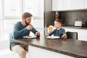 Handsome young father dressed in blue sweater eating at kitchen with his little son