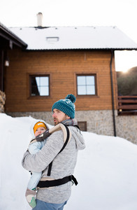 Handsome young father with his son outside on a walk, holding him in baby carrier. Sunny winter nature.