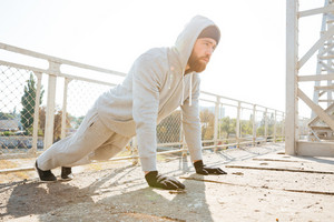 Handsome young fitness man doing push-up exercises outdoors at the urban bridge