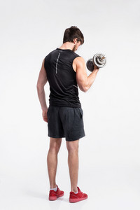 Handsome young fitness man in black sleeveless shirt working out with dumbbell. Studio shot on gray background. Rear view.