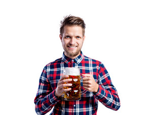 Handsome young hipster man in checked shirt holding a mug of beer. Oktoberfest. Studio shot on white background, isolated.