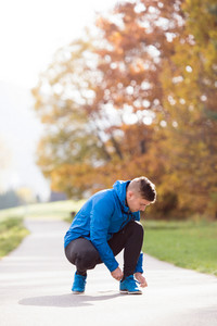 Handsome young hipster runner in blue jacket outside in colorful sunny autumn nature, tying shoelaces