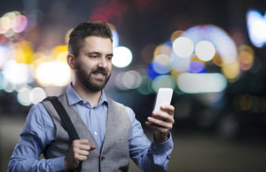 Handsome young hipster with his smartphone outside in the night city