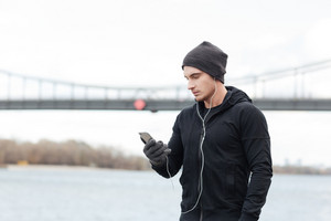 Handsome young man athlete in hat and gloves listening to music with cell phone outdoors