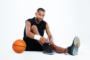 Handsome young man basketball player sitting and tying laces over white background