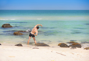 Handsome young man exercising at paradise beach in Phu quoc island, south of vietnam