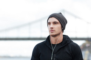 Handsome young man in hat listening to music with earphones outdoors