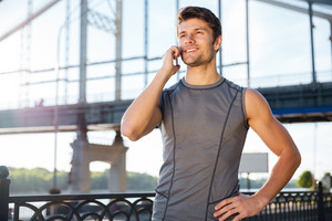 Handsome young man in sports uniform is talking on the mobile phone while standing at the bridge