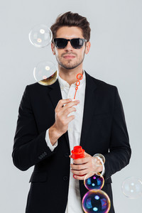 Handsome young man in sunglasses and black suit blowing soap bubbles over grey background