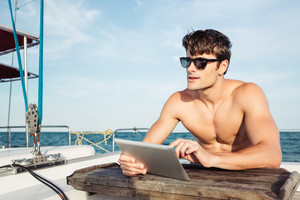 Handsome young man in sunglasses using tablet while sitting at the yacht