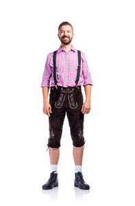 Handsome young man in traditional bavarian clothes. Oktoberfest. Studio shot on white background, isolated.