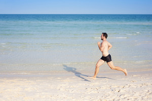 Handsome young man running at paradise beach in Phu quoc island, south of vietnam