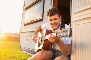 Handsome young man sitting in a camper van on a summer day
