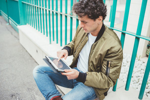 Handsome young man sitting outdoor in the city using tablet - technology, social network, city life concept
