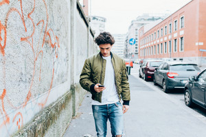 Handsome young man walking outdoor in the city using smart phone - technology, social network, city life concept
