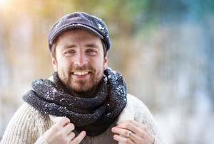 Handsome young man wearing woolen sweater in winter nature