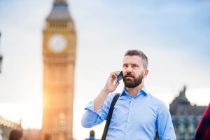 Handsome young man with smart phone on Westminster Bridge