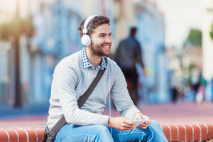 Handsome young man with white headphones outside in the town