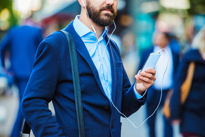 Handsome young manager with smartphone in London