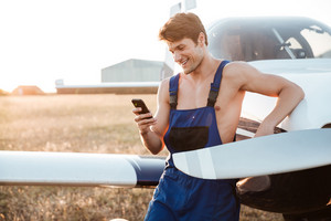 Handsome young mechanic in overall standing wirh smartphone near airplane landed on the field
