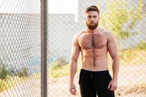 Handsome young shirtless fitness man during workout outdoors