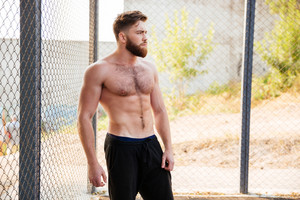Handsome young shirtless fitness man resting during workout outdoors