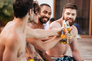 Handsome young smiling men having fun in swimming pool and drinking beer
