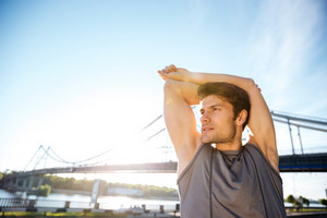 Handsome young sports man doing stretching at the bridge railing and looking away outdoors