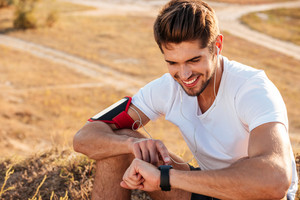 Handsome young sportsman sitting and using smart watch outdoors