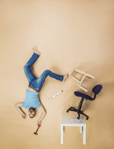 Handyman falling dangerously from a high pile of chairs. Studio shot on a beige background.