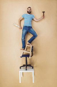 Handyman standing dangerously on a pile of chairs. Studio shot on a beige background.