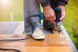 Handymen installing wooden flooring in patio, working with drilling machine